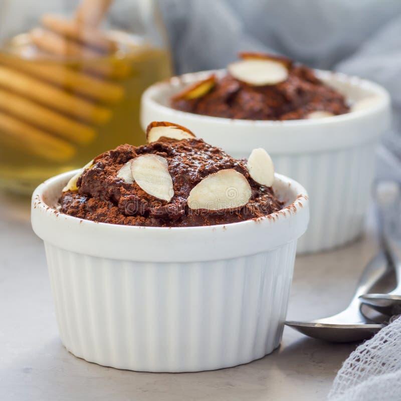 健康素食主义者自创点心用鲕梨,可可粉、香草、蜂蜜和杏仁挤奶,巧克力沫丝淋,方形的格式 免版税库存图片