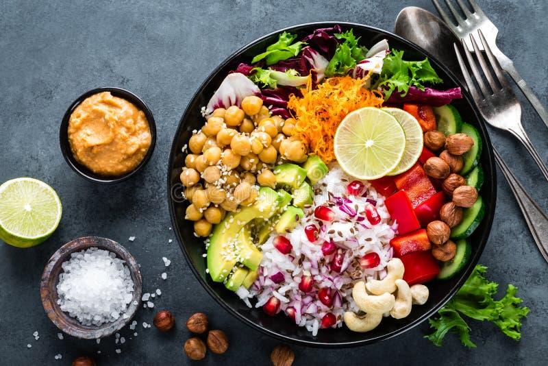 健康素食主义者菩萨碗用新鲜蔬菜沙拉,米,鸡豆,鲕梨,甜椒,黄瓜,红萝卜的石榴 免版税图库摄影