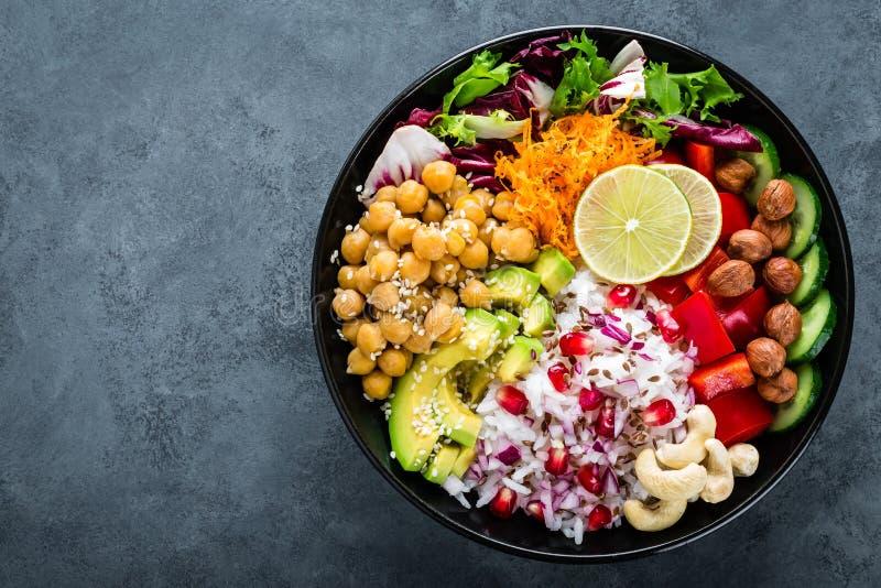 健康素食主义者菩萨碗用新鲜蔬菜沙拉,米,鸡豆,鲕梨,甜椒,黄瓜,红萝卜的石榴 免版税库存照片