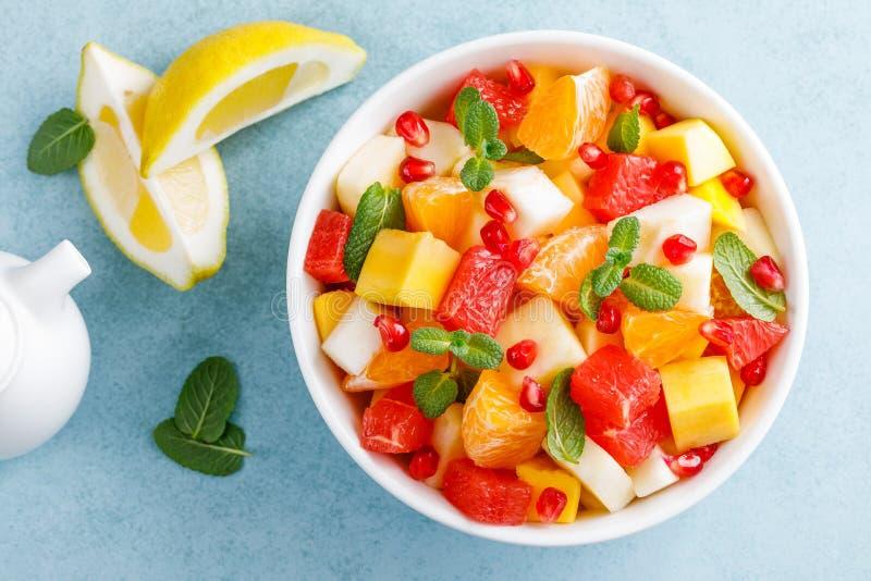 健康素食新鲜水果沙拉用苹果、梨、蜜桔、葡萄柚、芒果、石榴和柠檬汁 顶视图 免版税库存图片