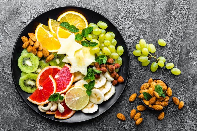 健康素食碗盘用新鲜水果和坚果 板材用未加工的苹果,桔子,葡萄柚,香蕉,猕猴桃,柠檬,葡萄, alm 库存照片