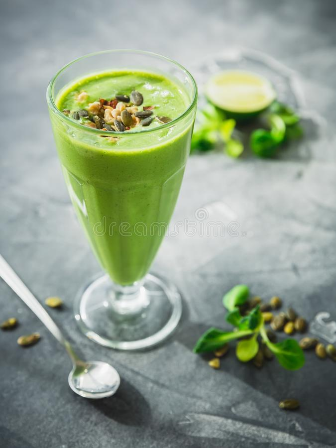 健康绿色圆滑的人用菠菜、香蕉和南瓜籽 免版税库存照片
