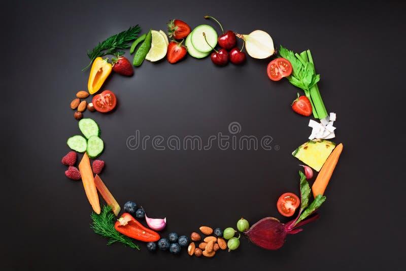 健康背景的食物 有机菜,果子,坚果,与拷贝空间的莓果圈子在黑黑板 顶层 库存图片