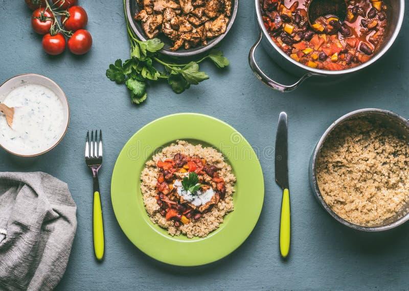 健康膳食用奎奴亚藜,蕃茄豆调味和在厨房用桌背景的炸鸡肉 库存图片