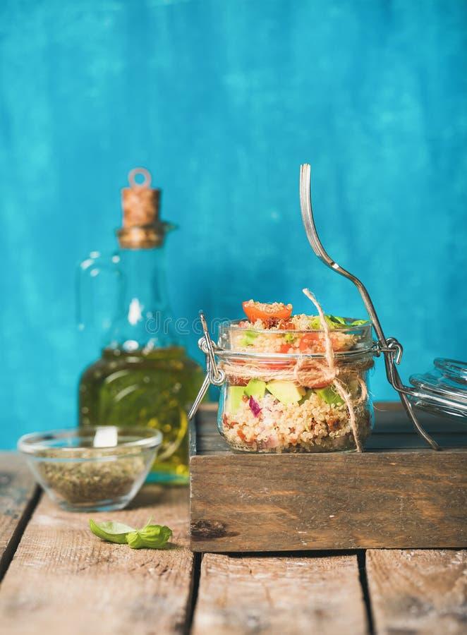 健康自创瓶子奎奴亚藜沙拉用蕃茄,鲕梨,新鲜的蓬蒿 免版税库存照片