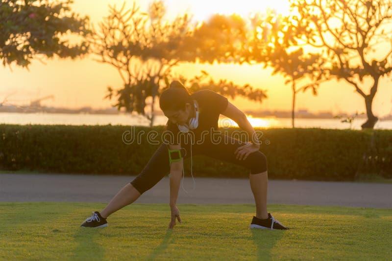 健康舒展做准备的赛跑者亚裔女子运动员腿在跑前在日落的公园 免版税库存照片