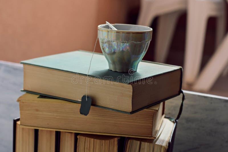 健康草本茶特写镜头在堆的老多灰尘的书 免版税库存照片