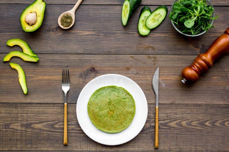 健康菜薄煎饼 菠菜薄煎饼服务用黄瓜、鲕梨和绿叶在黑暗的木背景上面 免版税库存图片