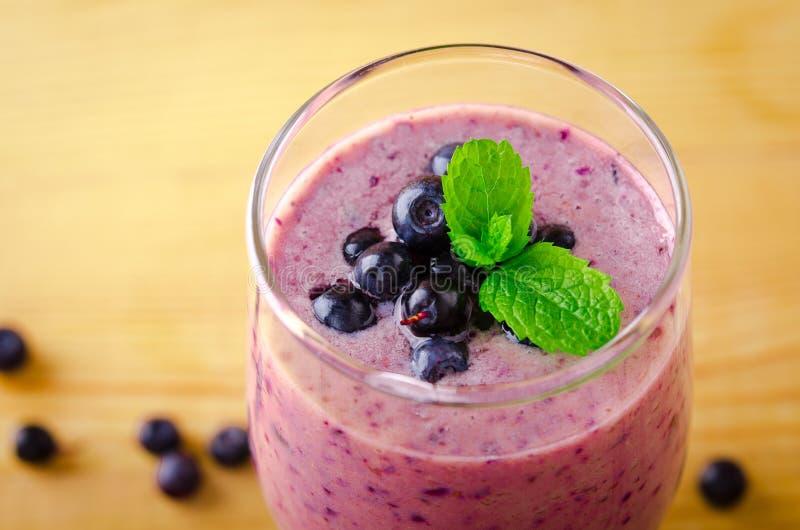 健康蓝莓香蕉圆滑的人用在玻璃的薄荷和新鲜的莓果 免版税库存照片
