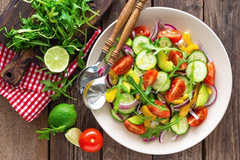 健康蔬菜菜肴、菜沙拉用新鲜的蕃茄,黄瓜、甜椒、红洋葱、鲕梨和芝麻菜 库存照片
