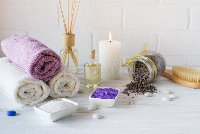 健康设置 紫色海盐、毛巾、按摩油、淡紫色花和蜡烛在白色织地不很细背景 免版税库存图片