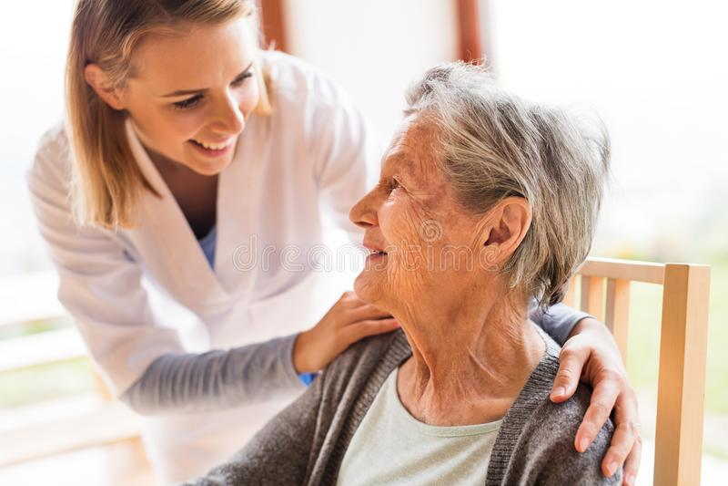 健康访客和一名资深妇女在家庭参观期间 免版税库存图片