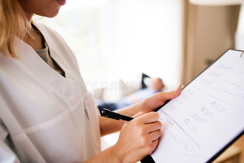 健康访客和老人在家庭参观期间 免版税库存照片