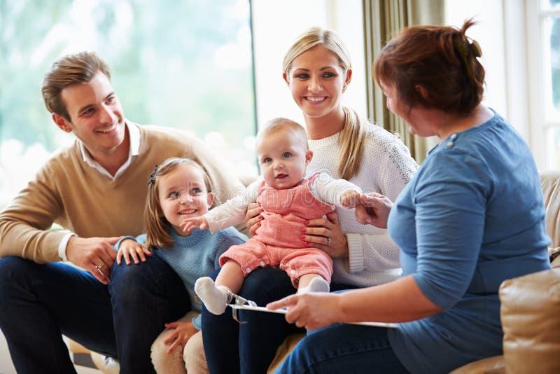 健康访客谈话与与年轻婴孩的家庭 免版税库存图片