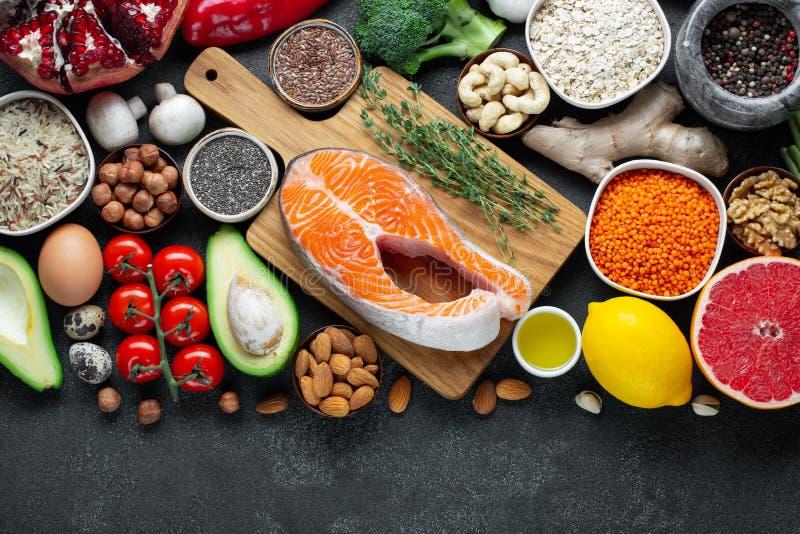 健康食品干净的吃选择:鱼,果子,坚果,菜,种子,superfood,谷物,在黑混凝土的蔬菜叶 库存图片