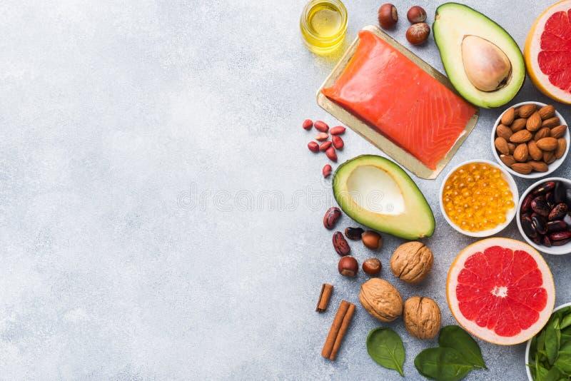 健康食品抗氧化产品:鱼和鲕梨、胡说和鱼油、葡萄柚菠菜和油在灰色具体背景 免版税图库摄影