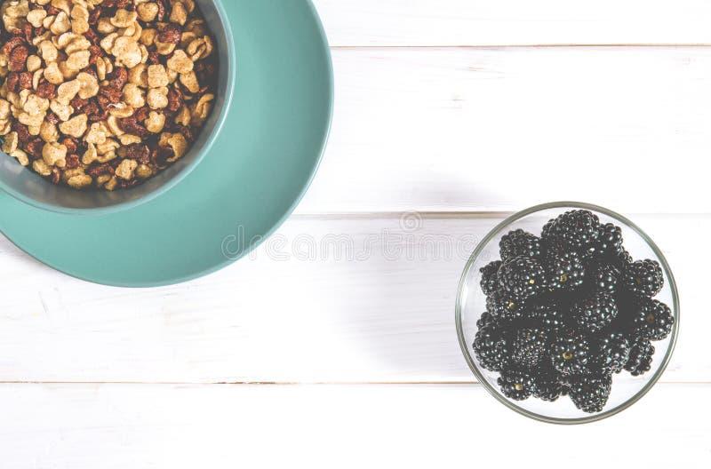 健康食品:玉米片和黑莓莓果一顿健康早餐在一张白色树桌上 库存图片