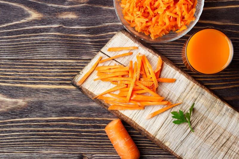 健康食品-切的红萝卜和红萝卜汁在木背景 免版税库存照片