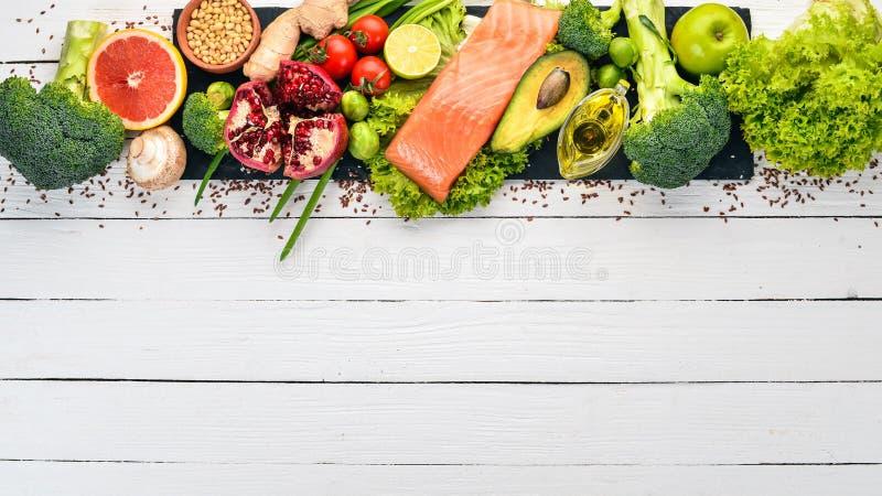 健康食品 鱼鲑鱼、鳄梨、西兰花、新鲜蔬菜、坚果和水果 在白色木制背景 库存照片