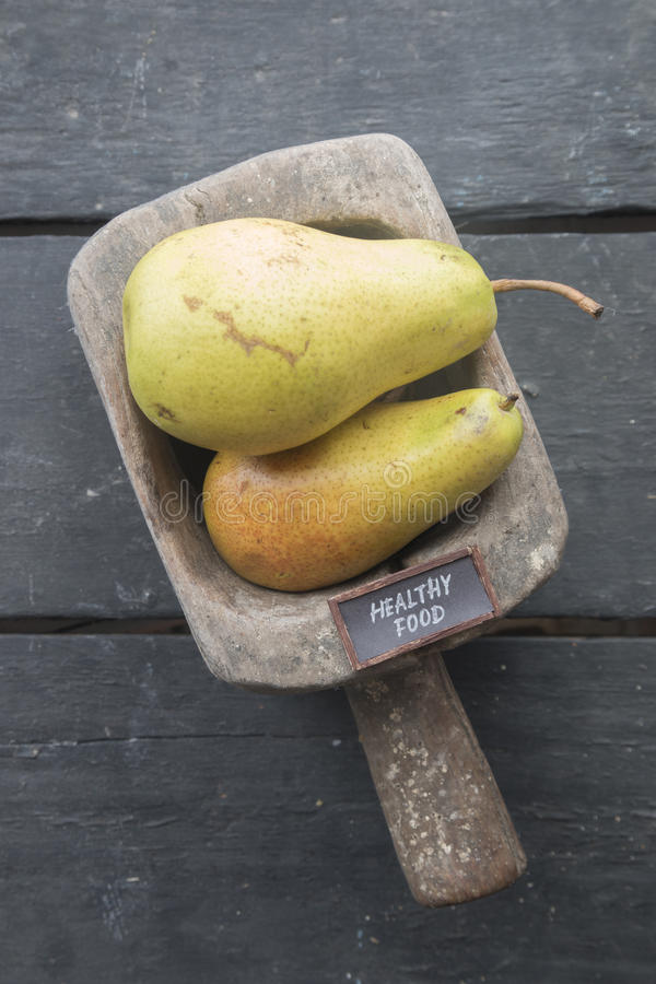 健康食物文本和水多的美味梨在葡萄酒背景 库存图片