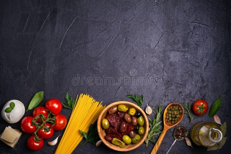 健康食物的选择 与意粉、无盐干酪帕尔马干酪、橄榄、蕃茄和迷迭香的意大利食物背景 免版税库存照片