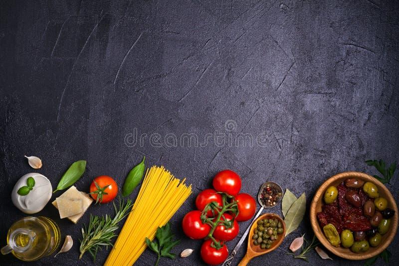 健康食物的选择 与意粉、无盐干酪帕尔马干酪、橄榄、蕃茄和迷迭香的意大利食物背景 免版税库存图片
