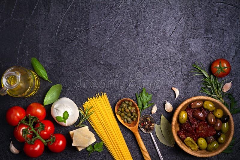 健康食物的选择 与意粉、无盐干酪帕尔马干酪、橄榄、蕃茄和迷迭香的意大利食物背景 库存图片