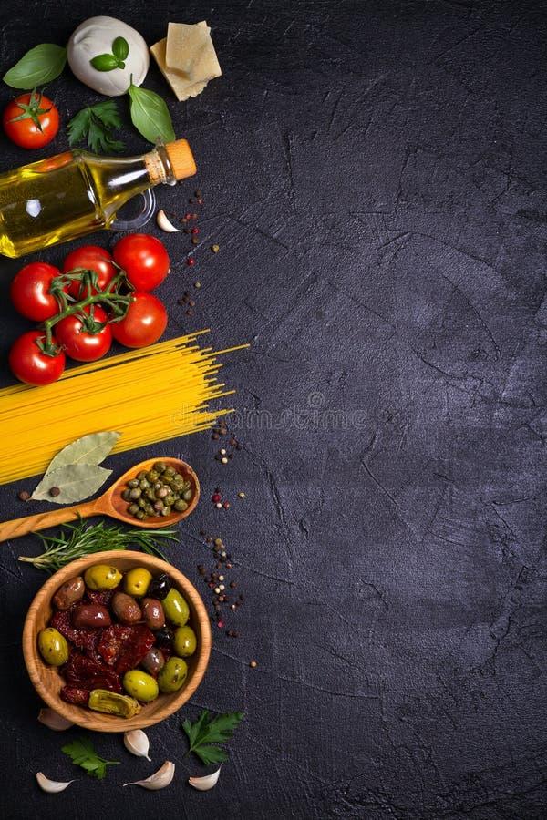 健康食物的选择 与意粉、无盐干酪帕尔马干酪、橄榄、蕃茄和迷迭香的意大利食物背景 免版税图库摄影