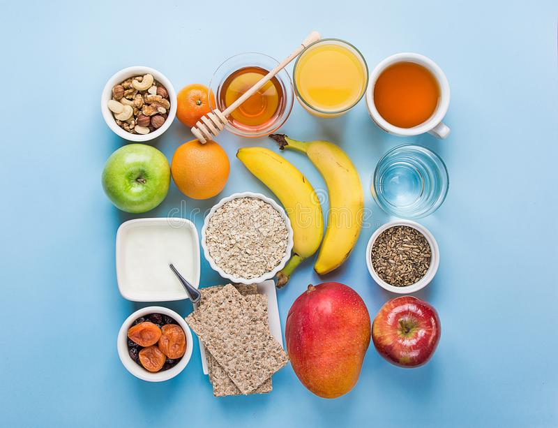 健康食物纤维来源早餐燕麦粥蜂蜜果子苹果香蕉芒果橙汁水绿茶坚果 浅兰的桌面 免版税库存照片