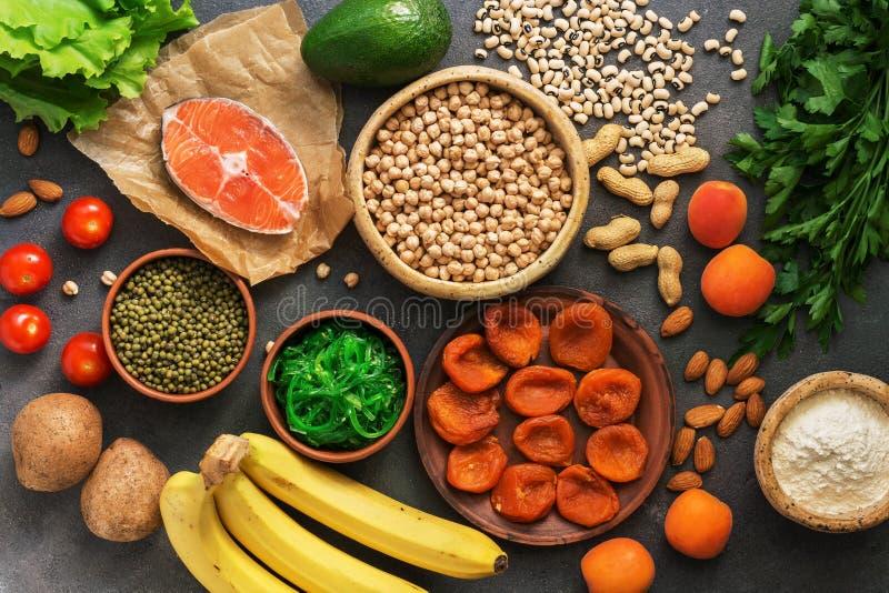 健康食物高在钾 各种各样的豆类、三文鱼、水果、蔬菜、杏干、海草chuka和坚果在a 免版税库存图片