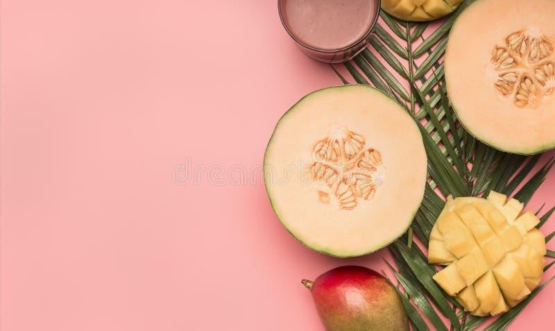 健康食物,热带水果,芒果,在monstera叶子的瓜有在桃红色背景,文本舱内甲板位置的空间的圆滑的人的 免版税图库摄影