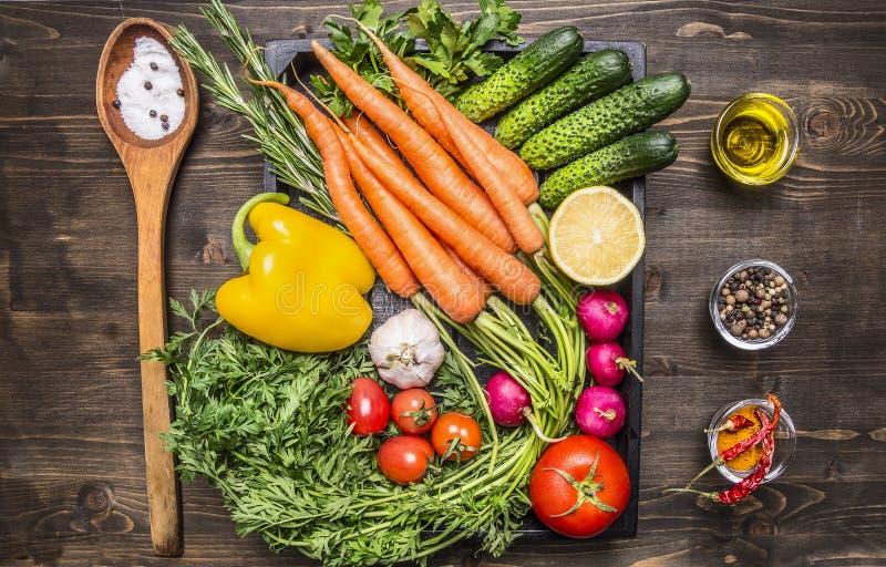 健康食物,烹调和素食概念新鲜的红萝卜西红柿,大蒜,黄瓜,柠檬,胡椒,萝卜,木匙子 免版税库存图片