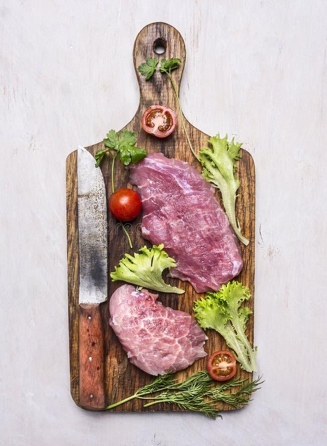 健康食物,烹调概念新鲜的猪肉牛排用沙拉,与一把刀子的蕃茄在白色的肉葡萄酒老切板的 免版税库存照片