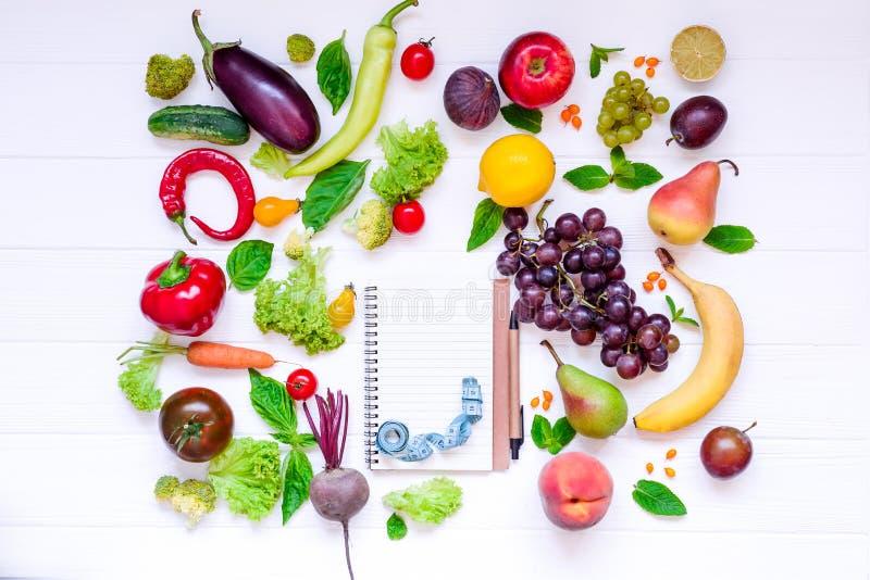 健康食物,饮食吃,戒毒所背景-不同的水果和蔬菜,倒空开放笔记本,并且在白色的测量的磁带求爱 库存图片