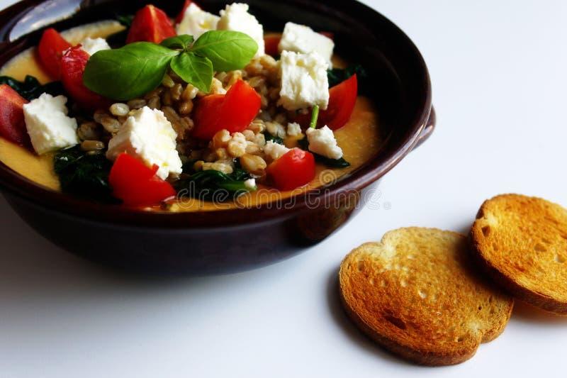 健康饭食碗光秃鹰嘴豆purée菠菜希腊白软干酪和西红柿 免版税库存图片
