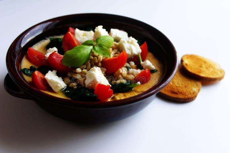 健康饭食碗被捣碎的鹰嘴豆几乎没有菠菜希腊白软干酪和西红柿 免版税库存图片
