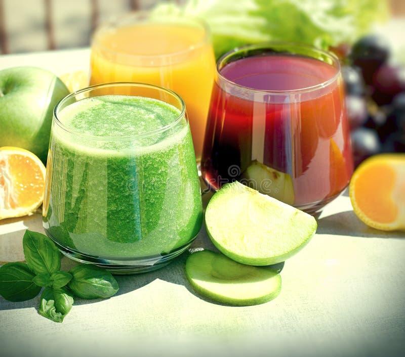 健康饮料-饮料做用新鲜的有机水果和蔬菜、绿色圆滑的人和果汁 免版税库存照片