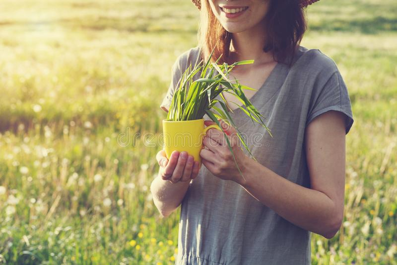 健康饮食,拿着有新鲜的绿草的愉快的年轻微笑的亭亭玉立的女孩黄色杯子 库存图片