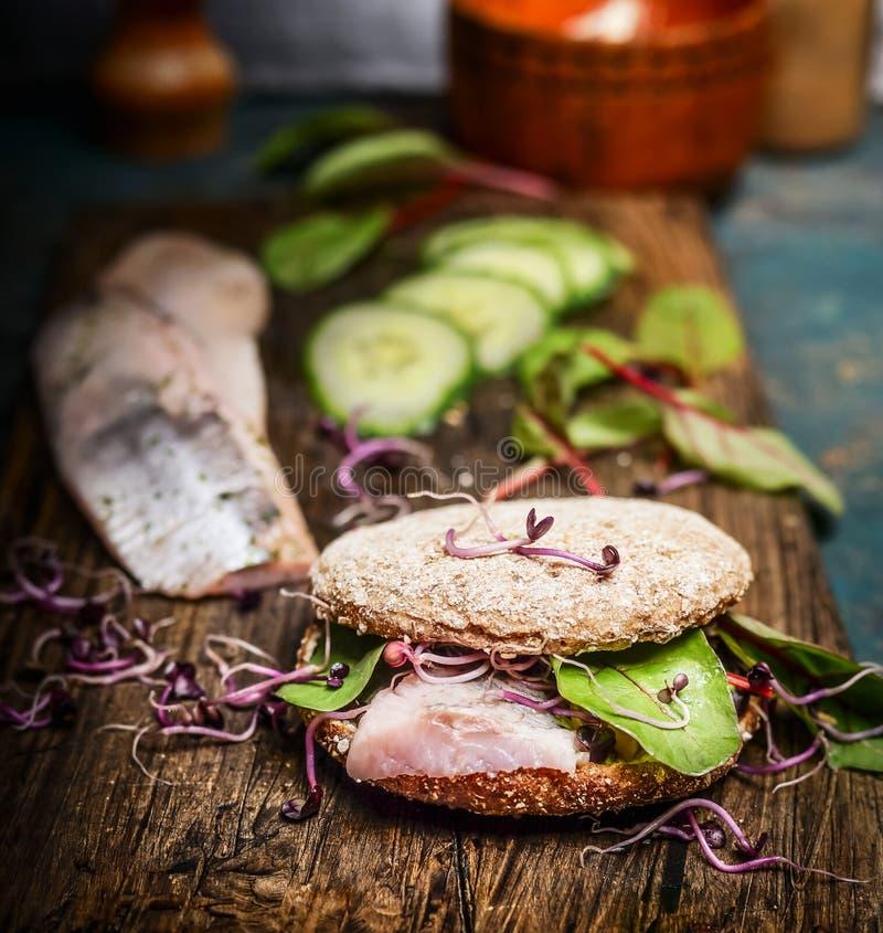 健康鱼三明治用鲱鱼、黄瓜和新芽在土气厨房用桌上 免版税库存图片