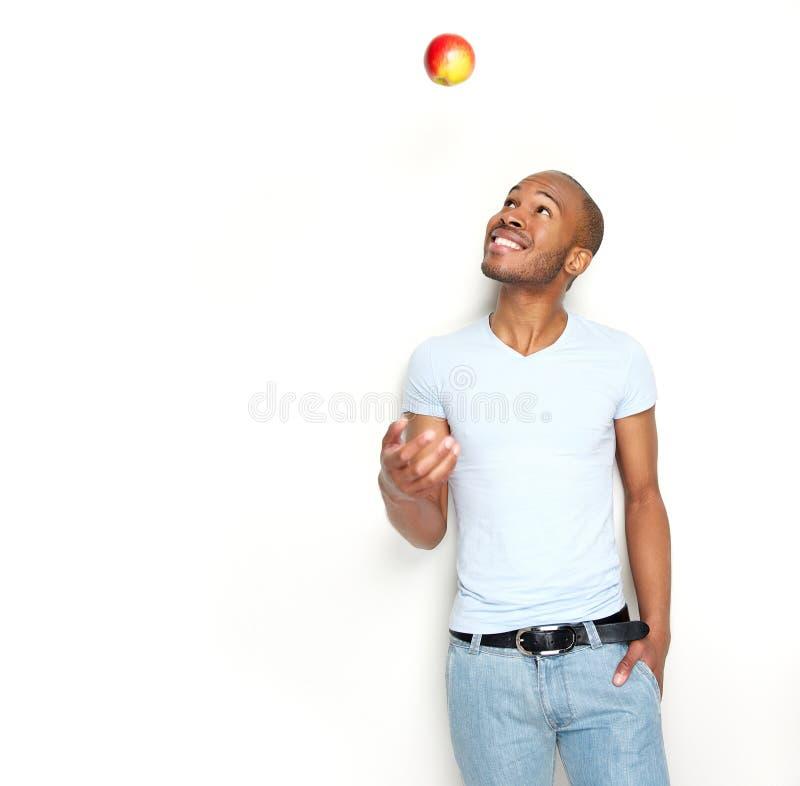 健康年轻人投掷的苹果在天空中 免版税库存图片