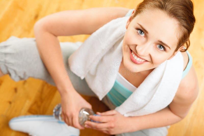 健康年轻在健身房的女运动员饮用水 免版税库存照片