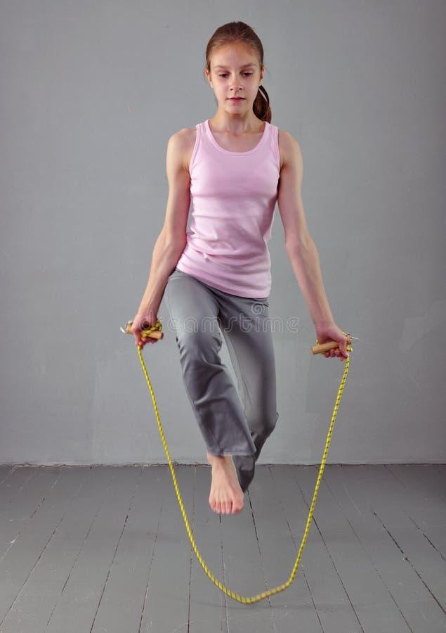 健康年轻肌肉十几岁的女孩跨越横线在演播室 行使与跳跃的孩子在灰色背景 图库摄影
