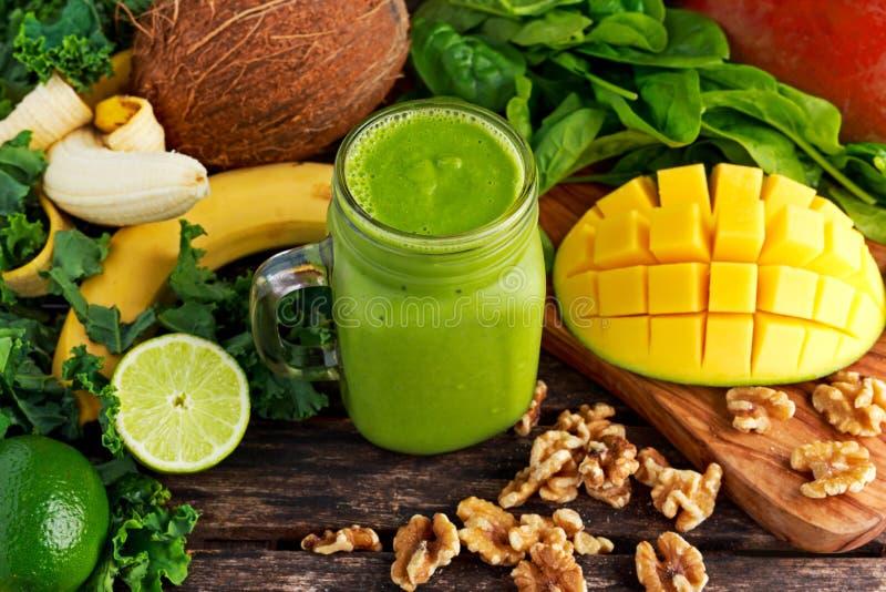 健康绿色伸手可及的距离维生素圆滑的人用婴孩叶子菠菜,无头甘蓝、芒果、香蕉、石灰、核桃和椰子浇灌 免版税库存图片
