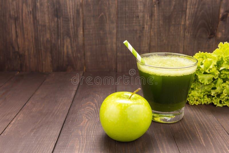 健康绿色圆滑的人用在土气木背景的苹果 库存图片