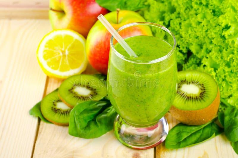 健康绿色圆滑的人用菠菜、猕猴桃、苹果、沙拉和薄菏在玻璃 图库摄影