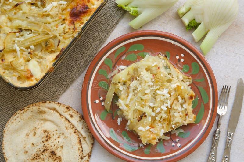 健康素食晚餐:烤箱被烘烤的茴香电灯泡用土豆 免版税库存照片