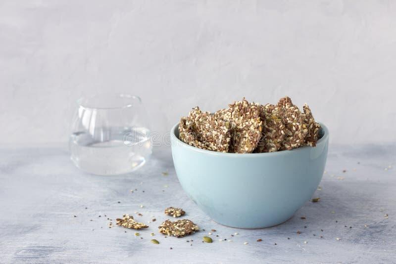 健康multigrain gluten-free薄脆饼干,能转化为酮,从chia种子、胡麻、芝麻和地面在陶瓷碗的南瓜籽 库存照片