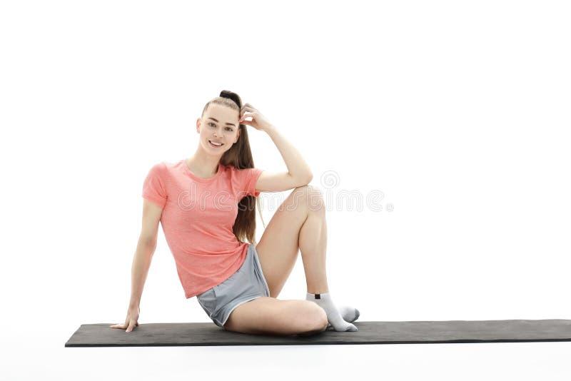 健身、体育、人们和健康生活方式概念-做在莲花姿势的妇女瑜伽凝思在席子 免版税库存照片