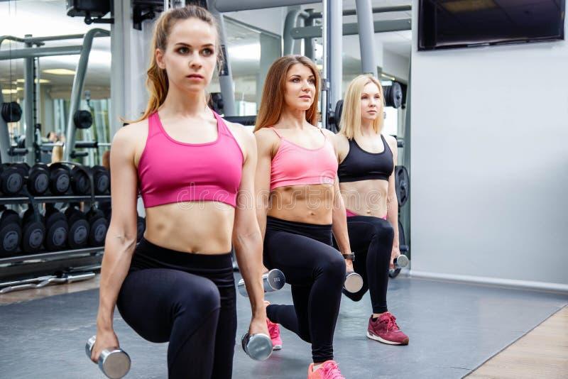 健身、体育、友谊和健康生活方式概念-做与重量的小组可爱的少妇刺在健身房 库存照片