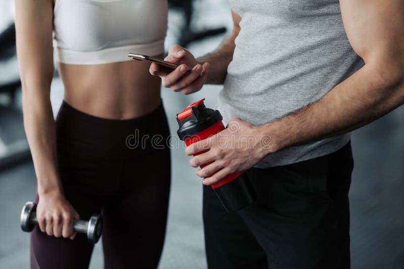 健身、体育、技术和减肥概念-关闭微笑的年轻女人和个人教练员用智能手机和水 免版税库存照片